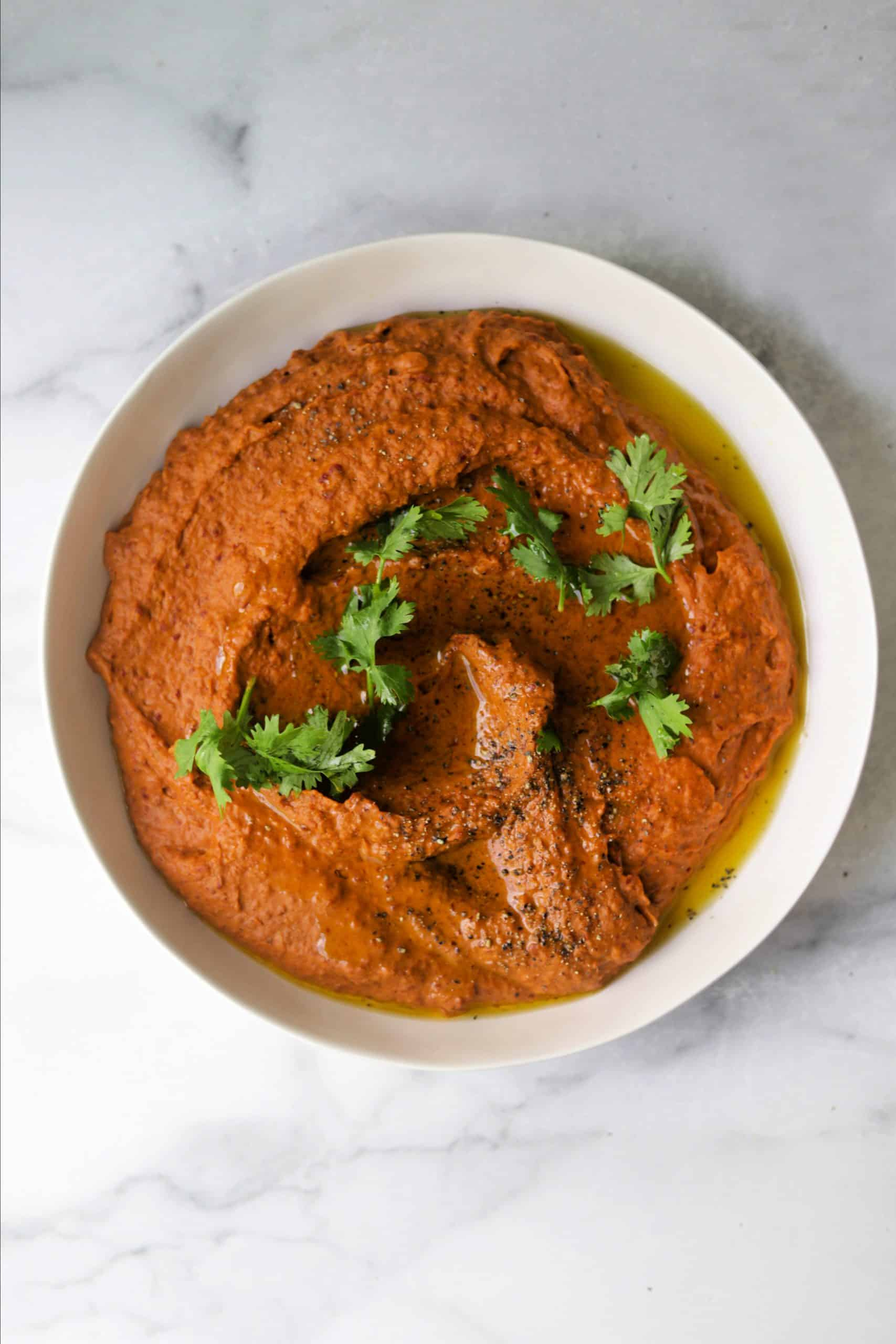 A white bowl filled with chili hummus with cilantro on top.
