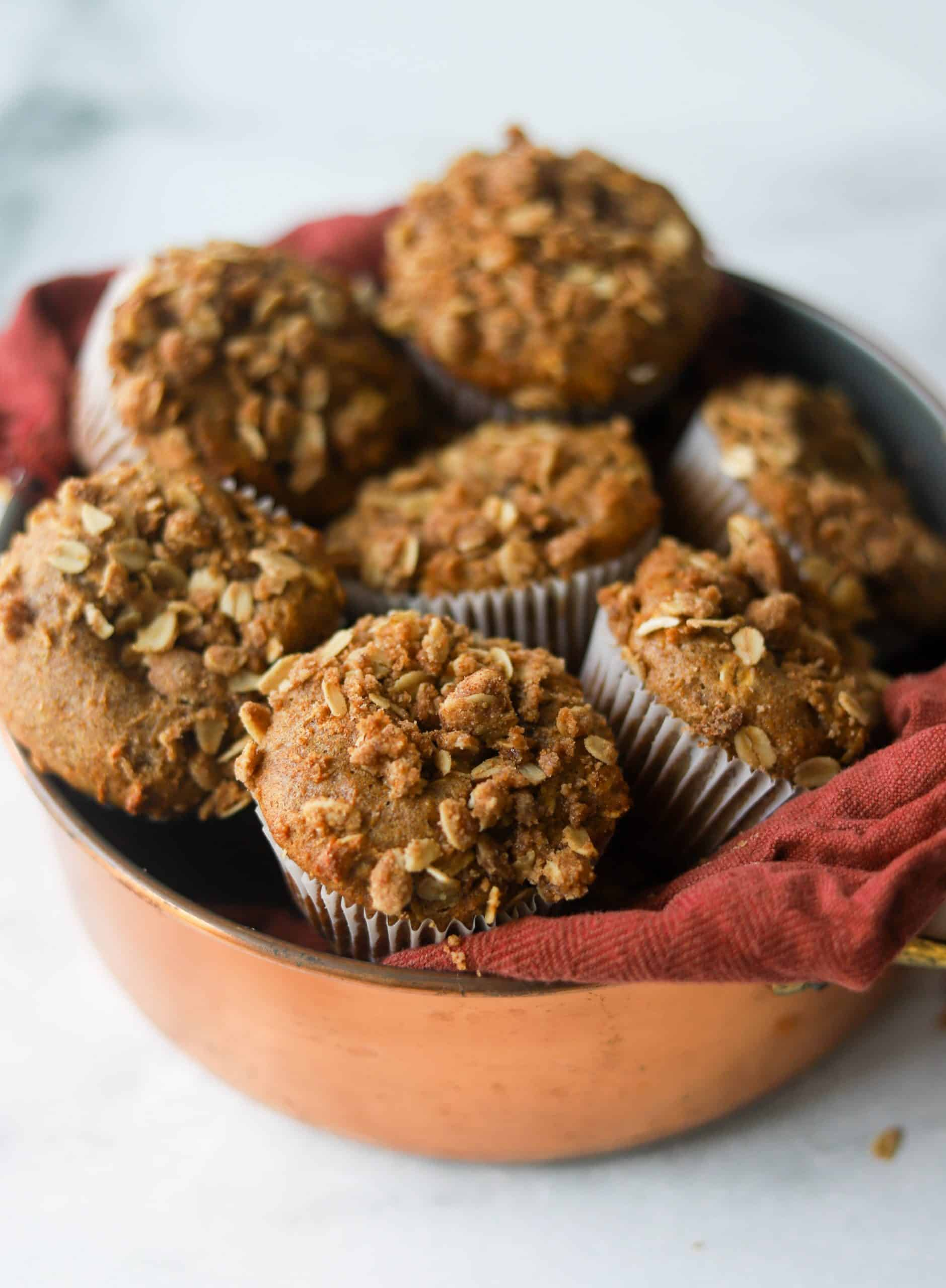 A copper basket filled with coffee cake muffins inside a burnt orange cloth.