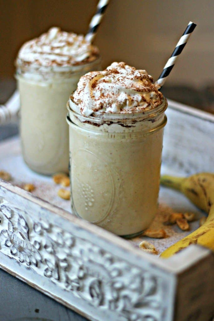 Side shot of two peanut butter banana shakes with whipped cream.