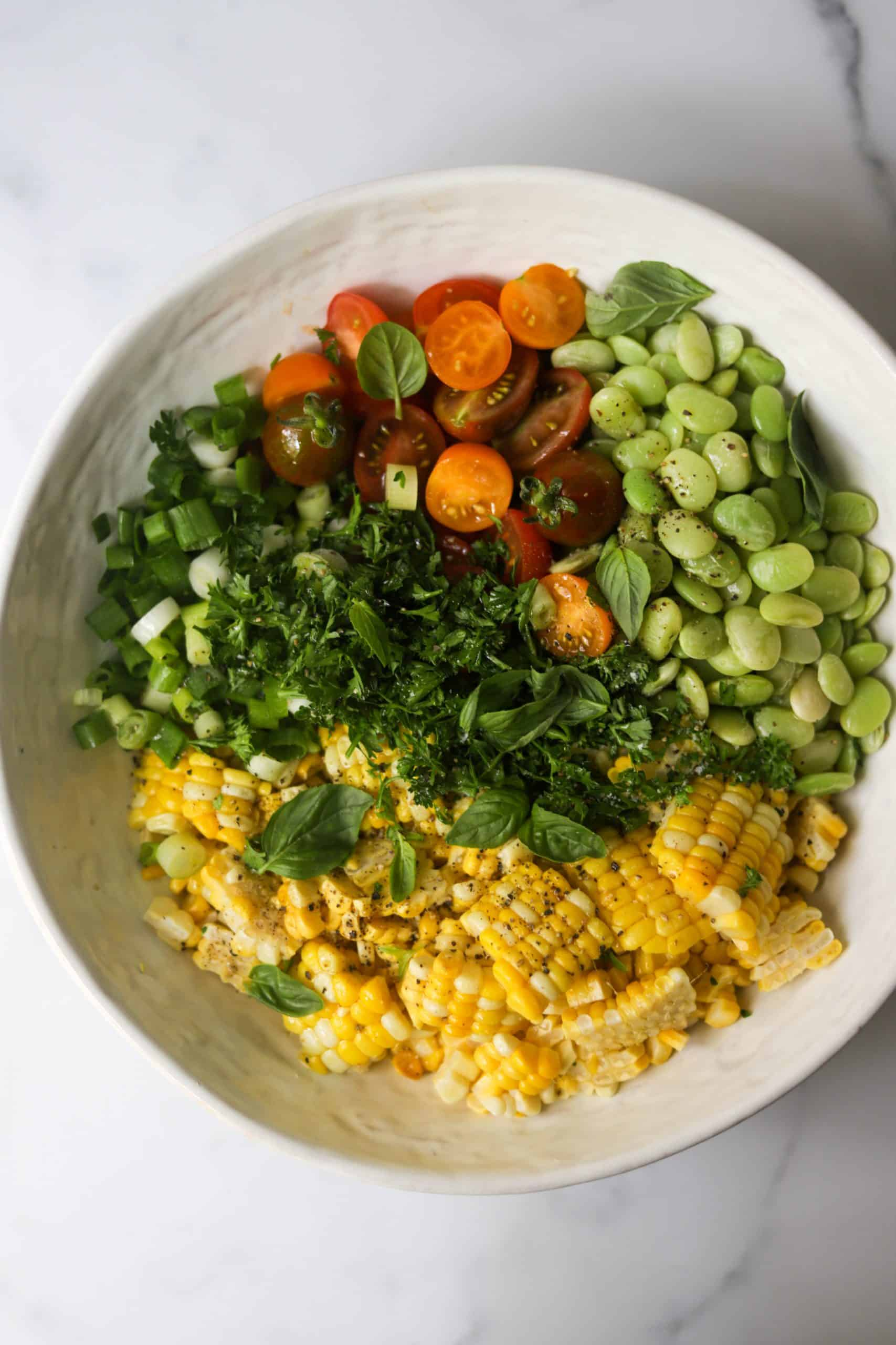 A white bowl filled with summer succotash.
