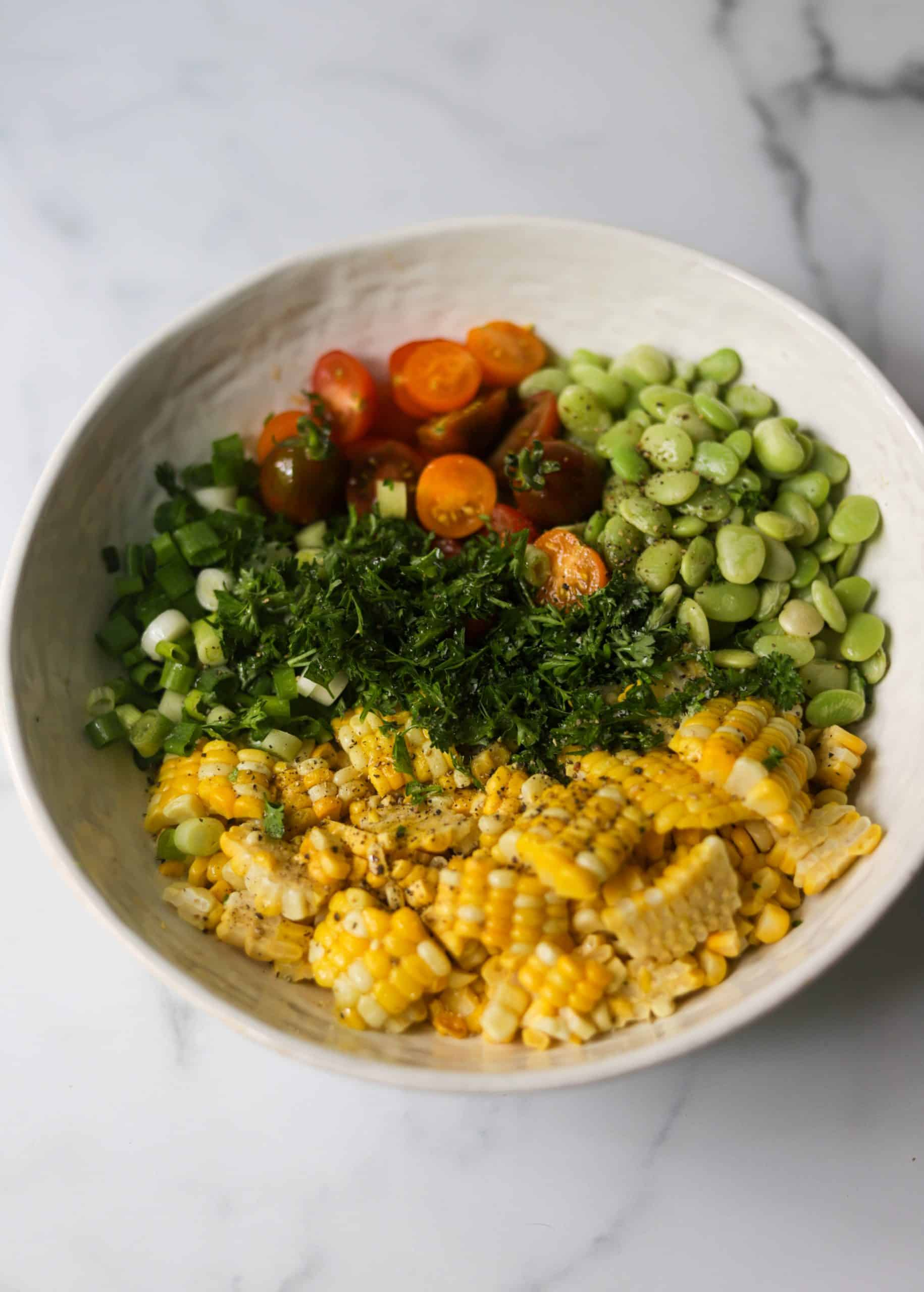 A white bowl filled with sweet corn salad ingredients.