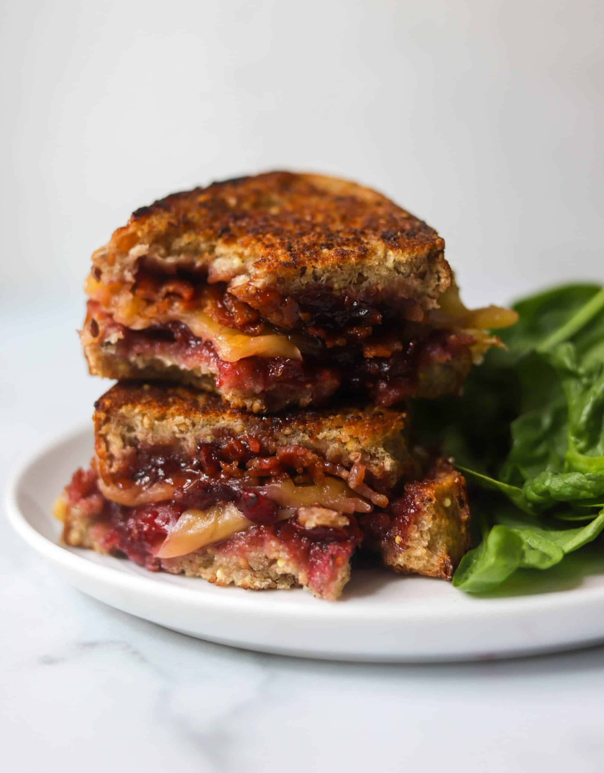 Cherry bacon grilled cheese on a white plate with spinach salad.