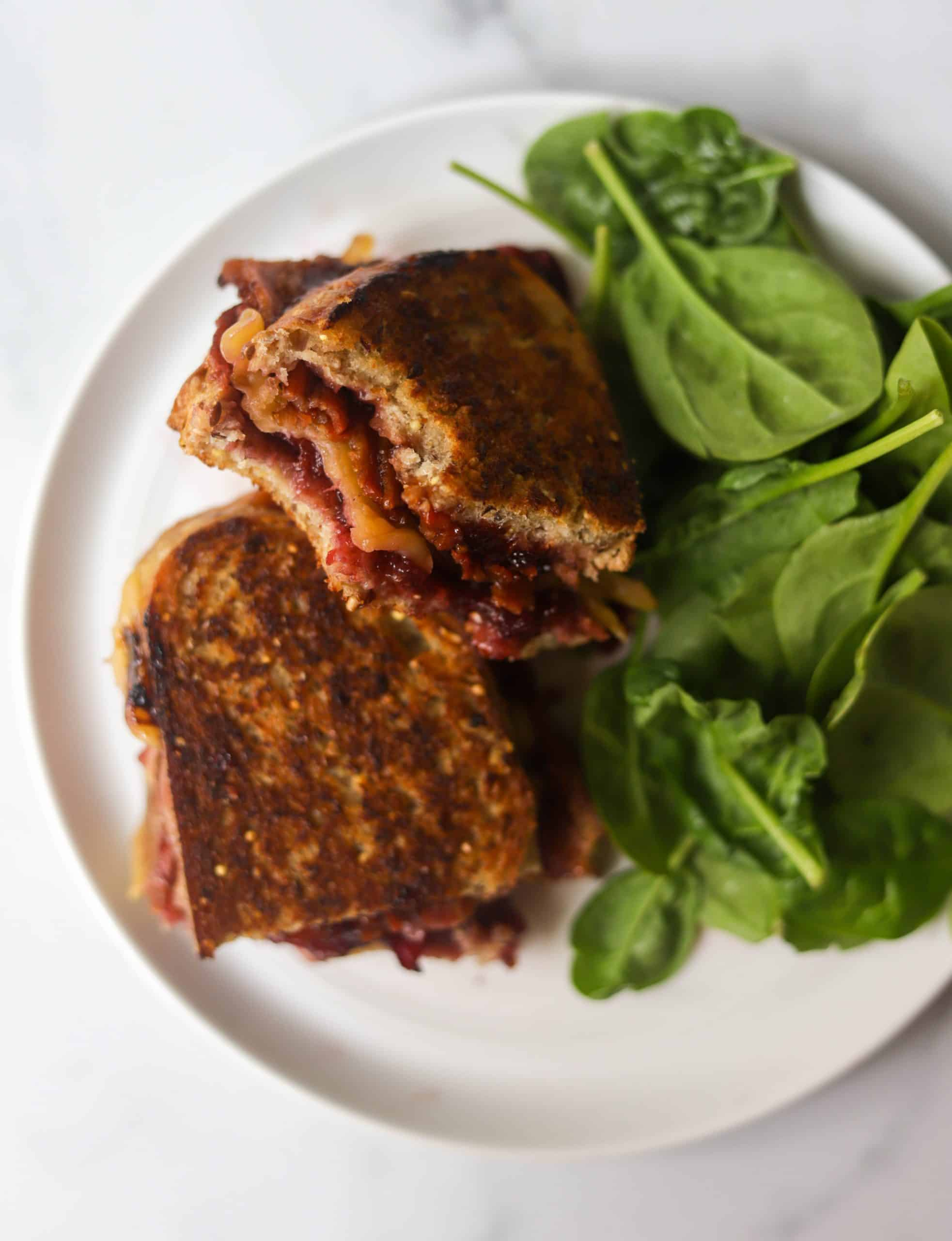 A birds eye view of a grilled cheese sandwich and spinach salad.