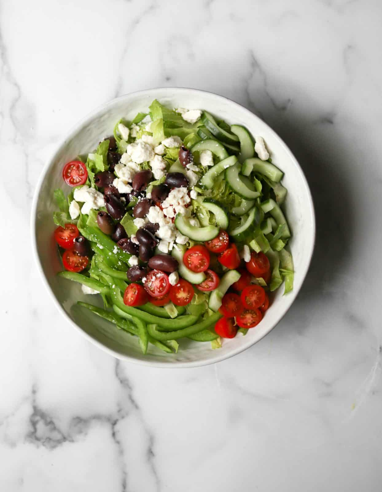 Greek salad in white bowl filled with a variety of vegetables