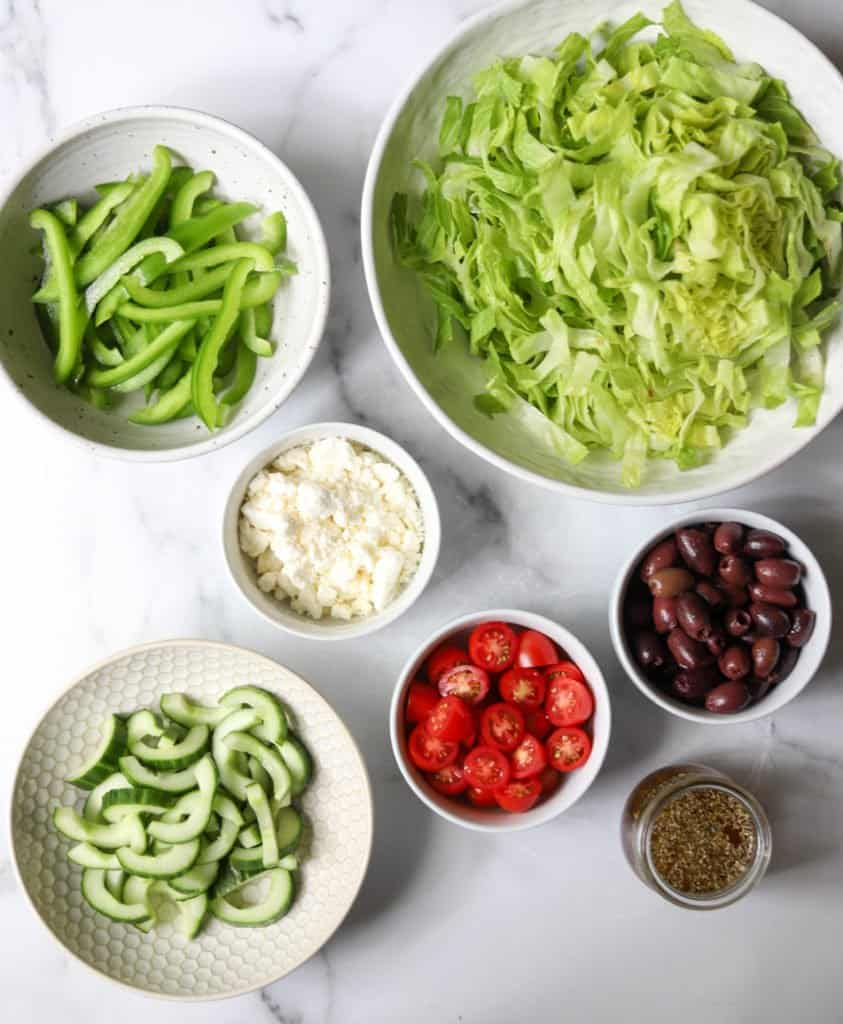 Greek salad ingredients in white bowls