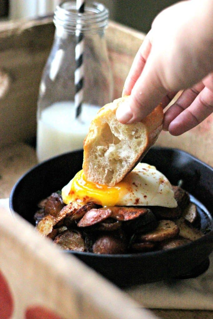 Chicken sausage potato hash on a skillet with bread dipping into an egg