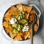 Chicken taco casserole in a white dish with a serving spoon.