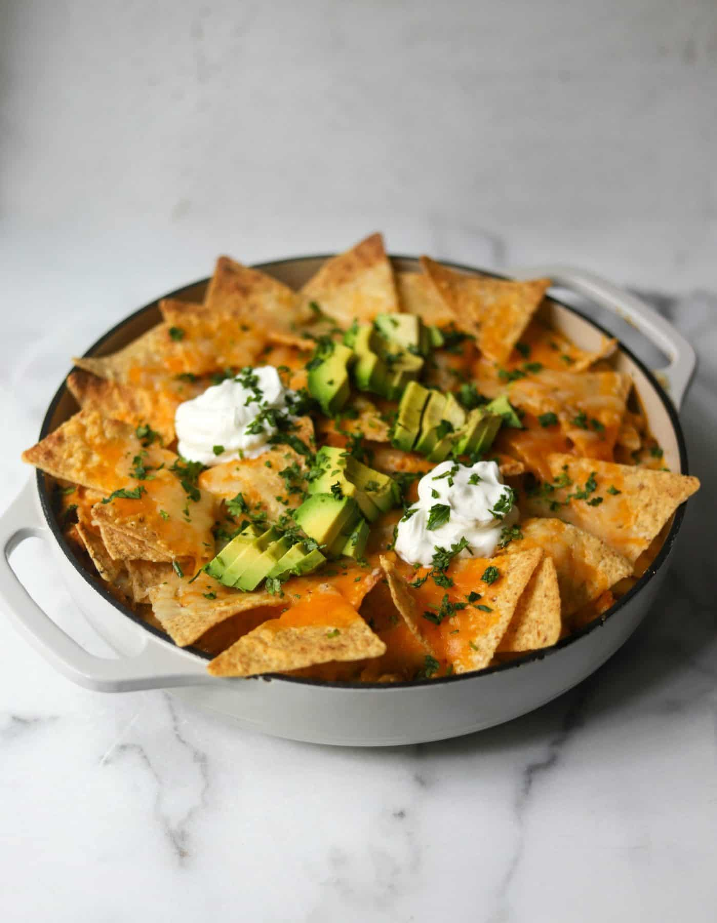 Chicken casserole in a white baking dish topped with tortilla chips, sour cream, avocado, and cheese.