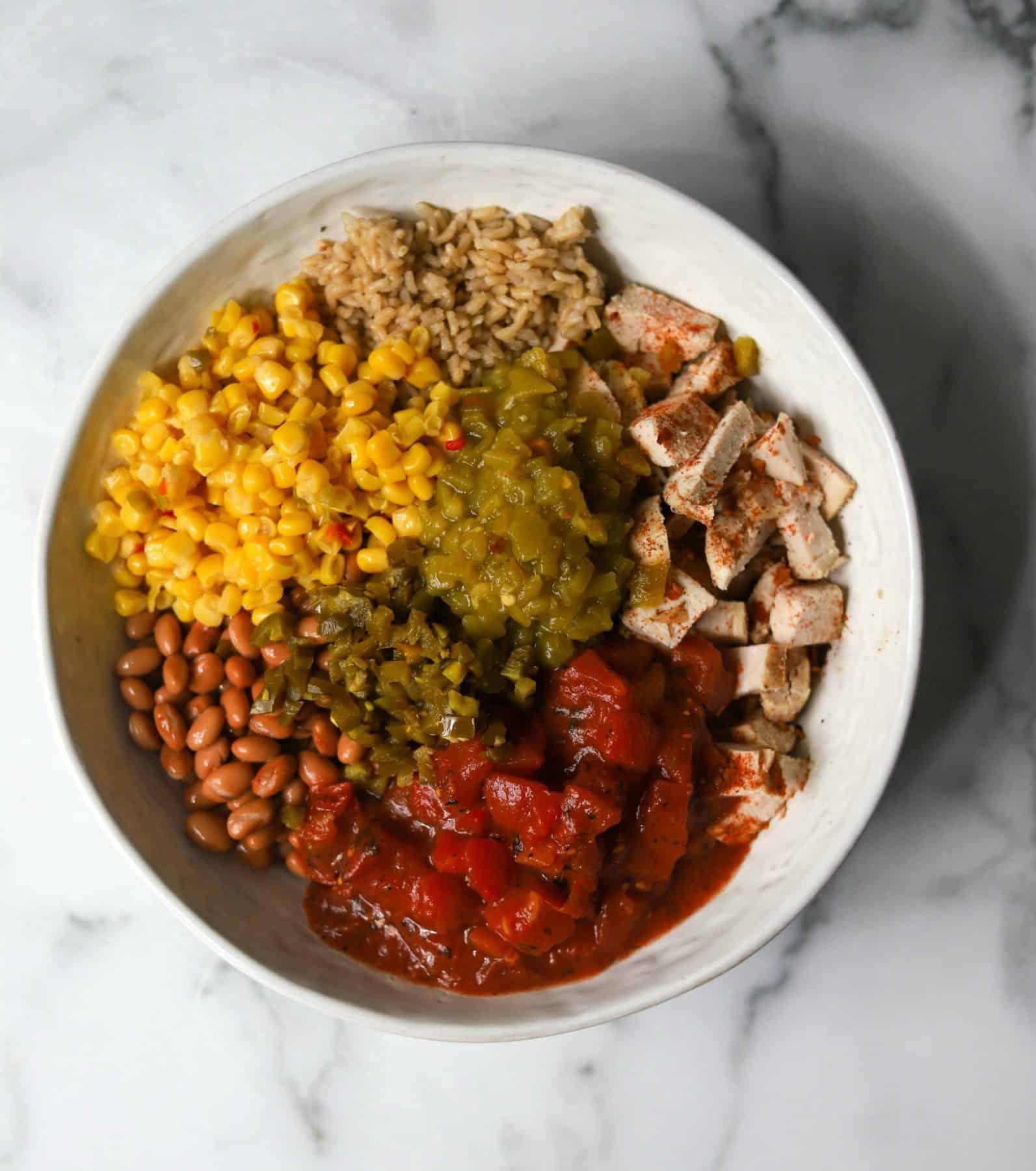 Chicken taco casserole ingredients in a white bowl.