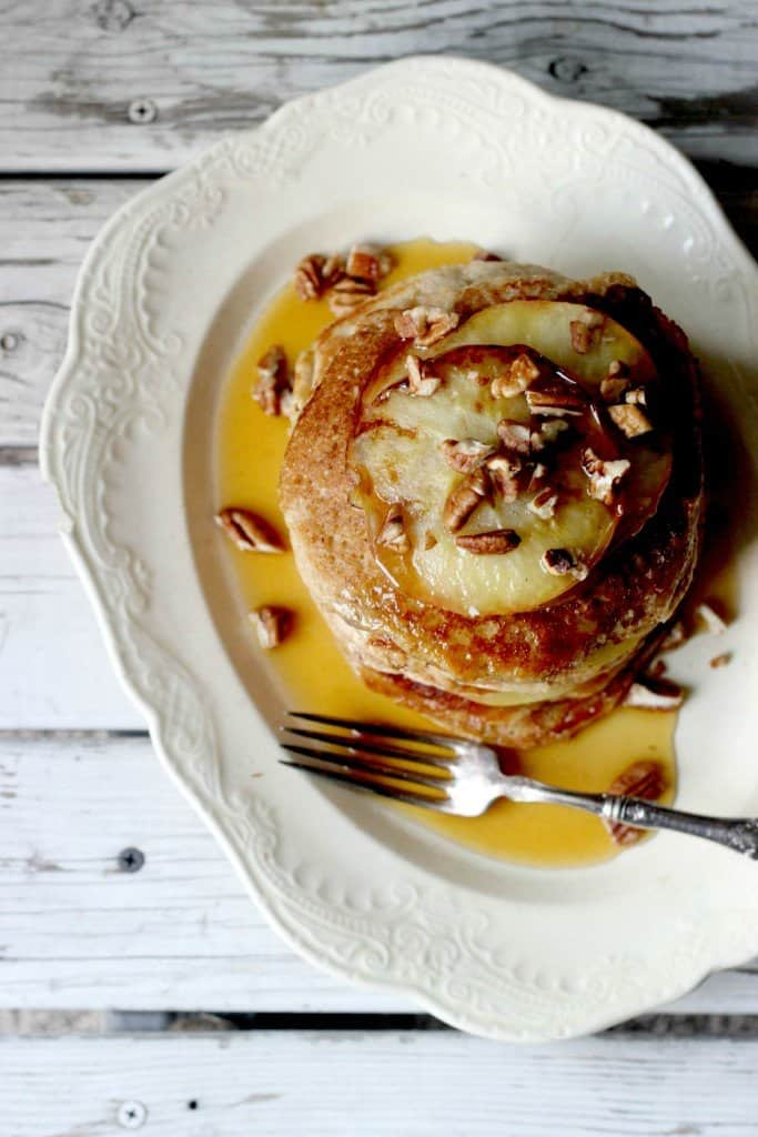 Overhead shot of pancakes on a white plate.
