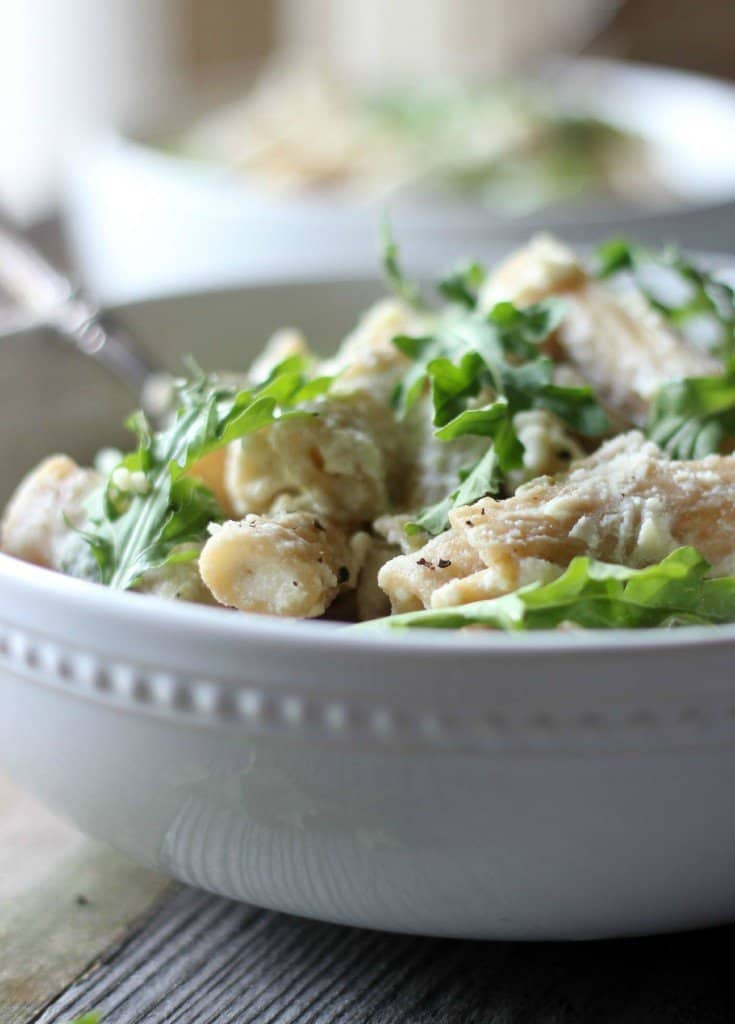 Lemon Ricotta Pasta in a white bowl with arugula.