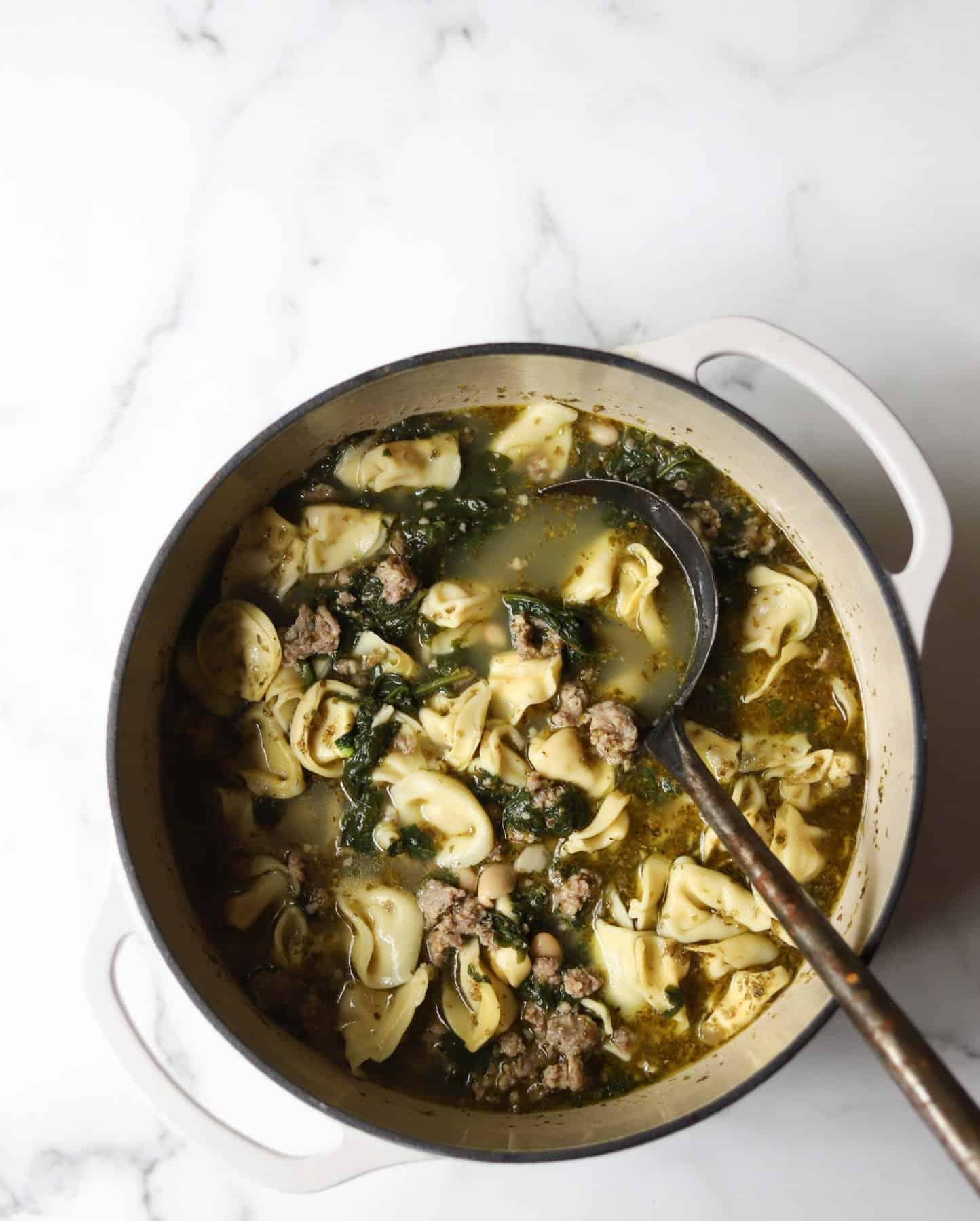 Tortellini soup in a white pot