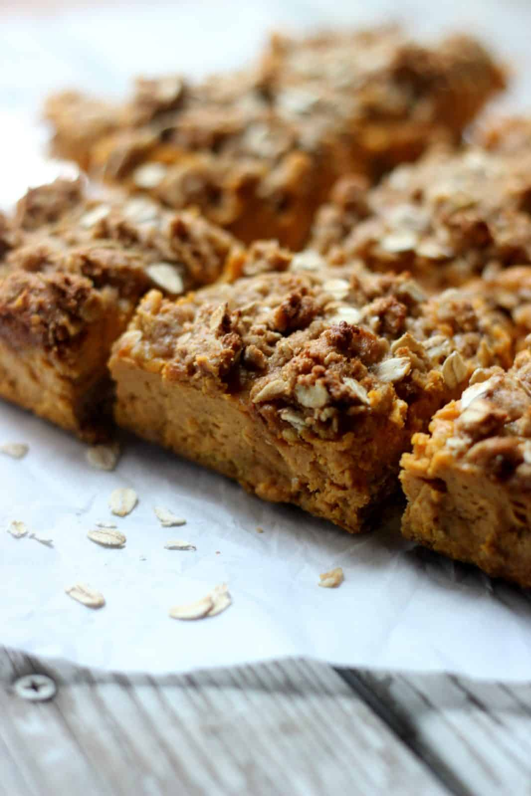 Close-up shot of pumpkin crumb bars on white parchment paper.