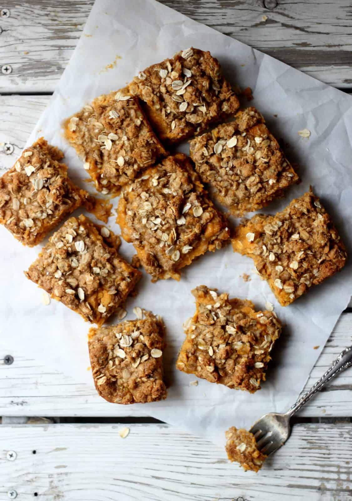 Overhead shot of pumpkin crumb bars on white parchment paper.