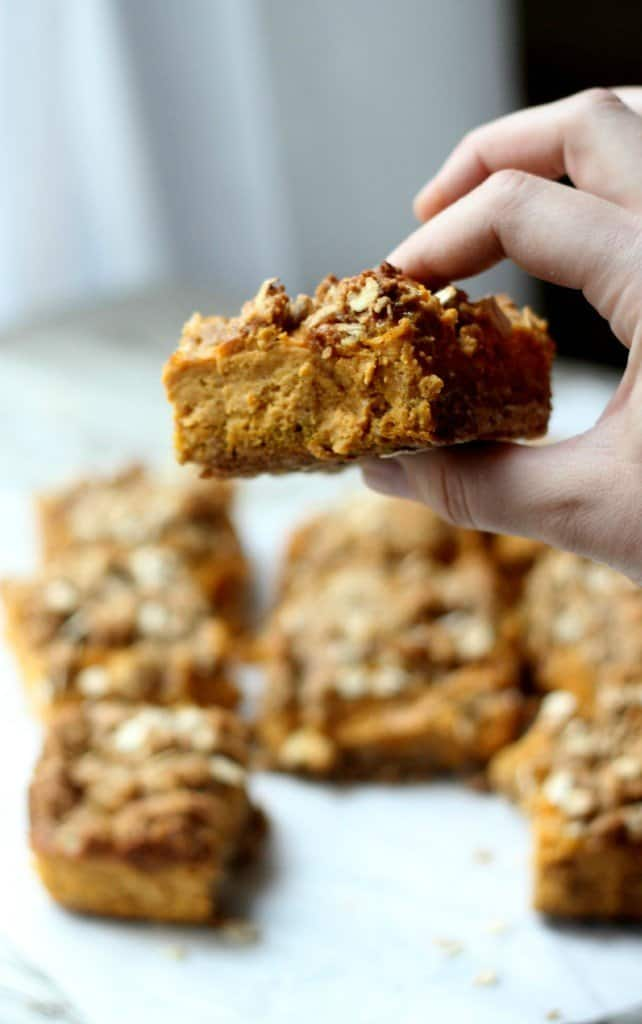 Hand holding one pumpkin crumb bar with others in the background.