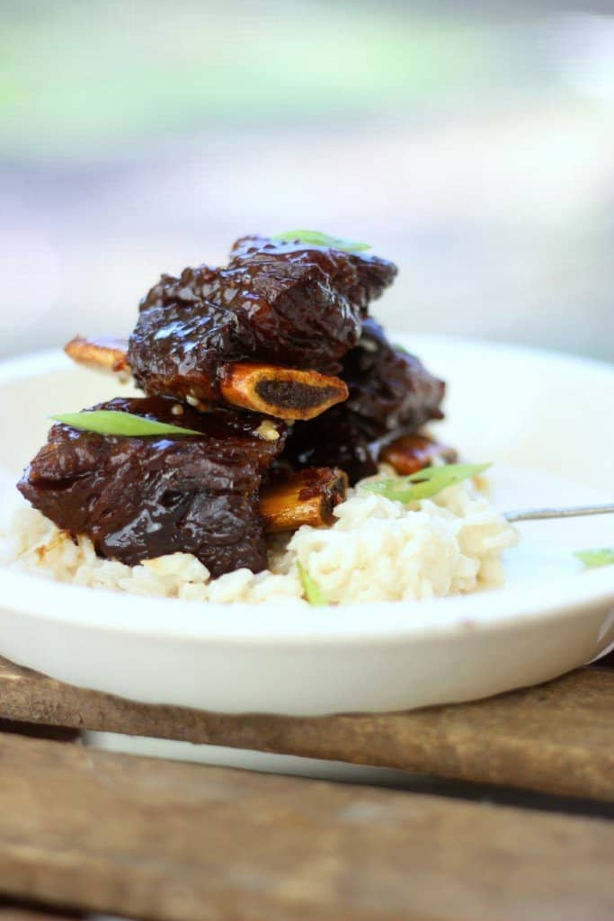 Side shot of ginger beef short ribs on top of rice in a white bowl.