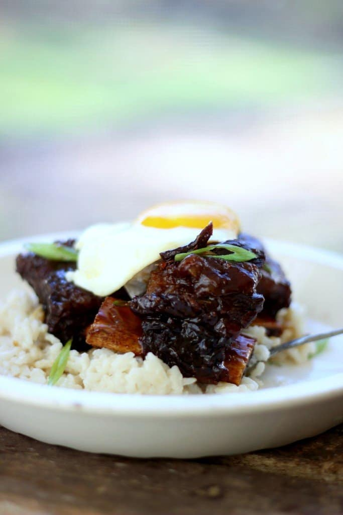Side close-up shot of ginger beef short ribs on top of rice in a white bowl with an egg on top.