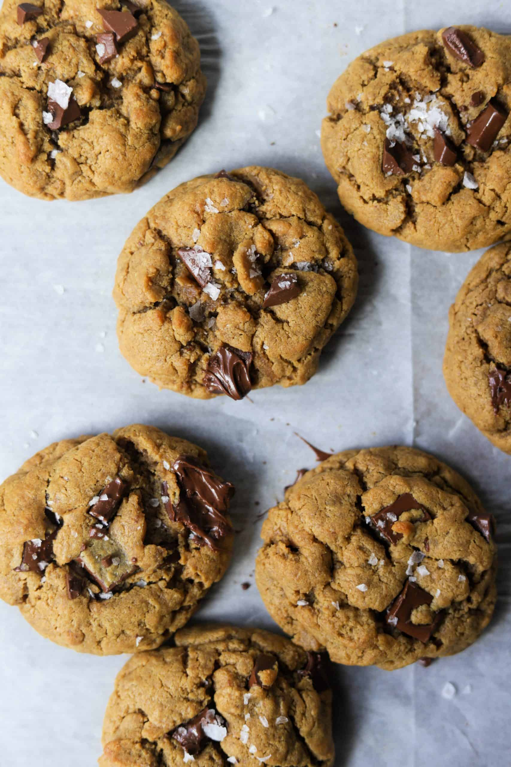 Several peanut butter cookies with chocolate chunks on parchment paper.