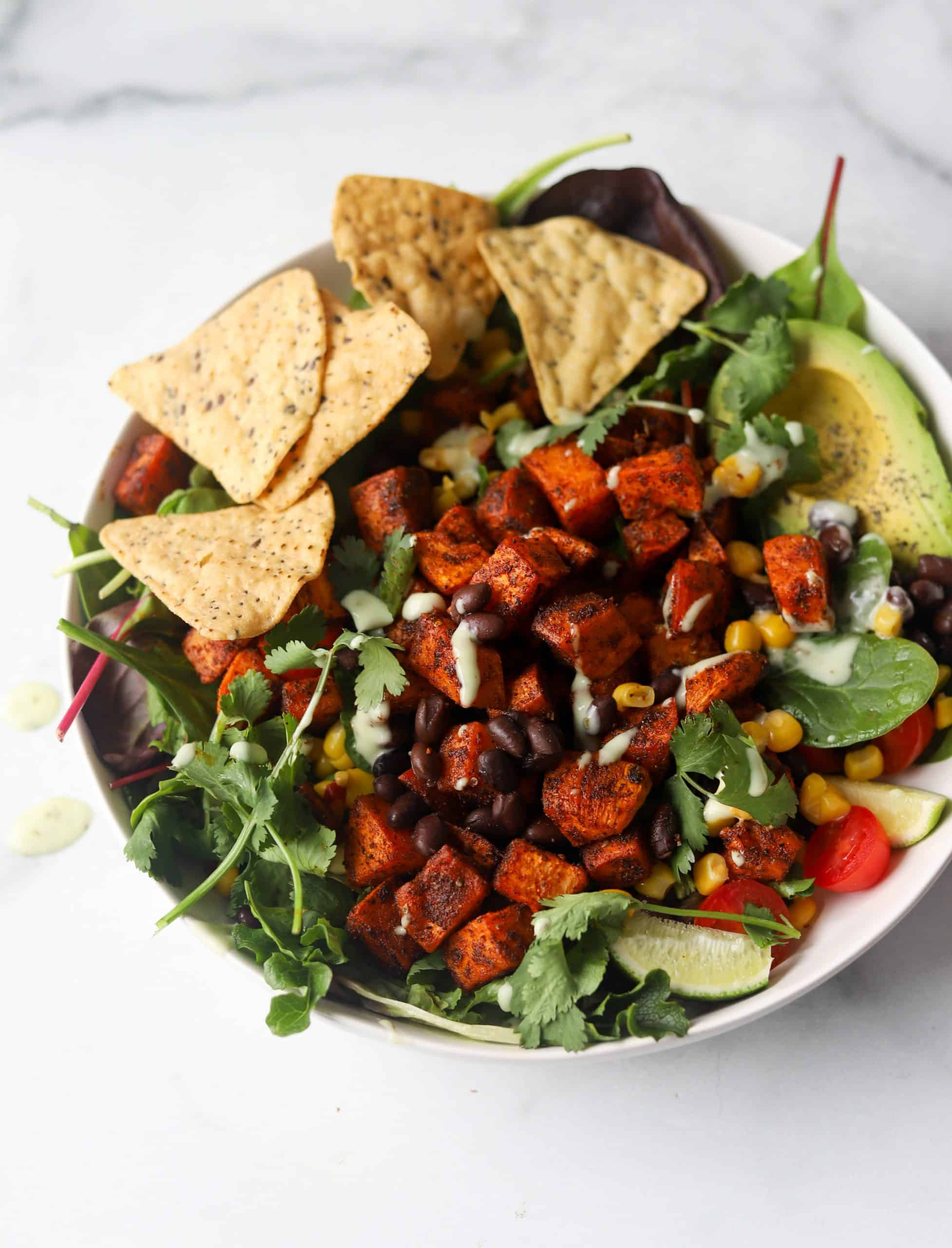 Roasted sweet potatoes and taco salad fixings in a white bowl.