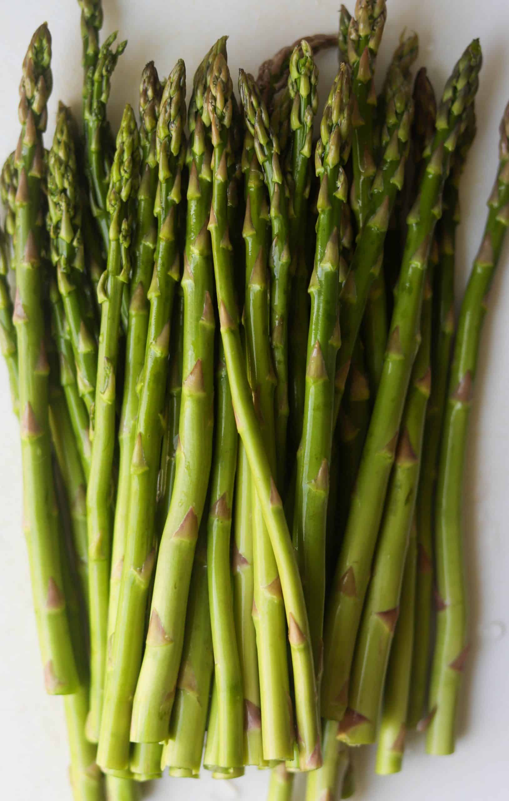 A bunch of asparagus on a white cutting board.