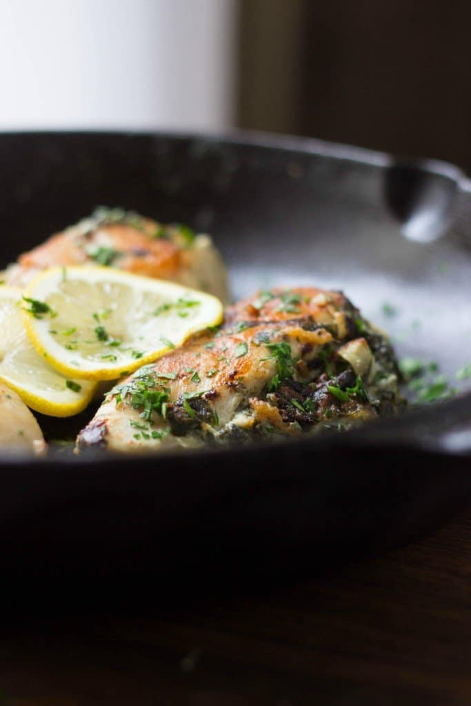 Close up of spinach artichoke stuffed chicken in a skillet