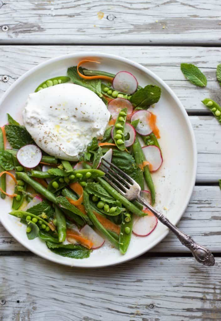 Overhead shot of spring veggie and burrata salad in a white plate with a silver fork.