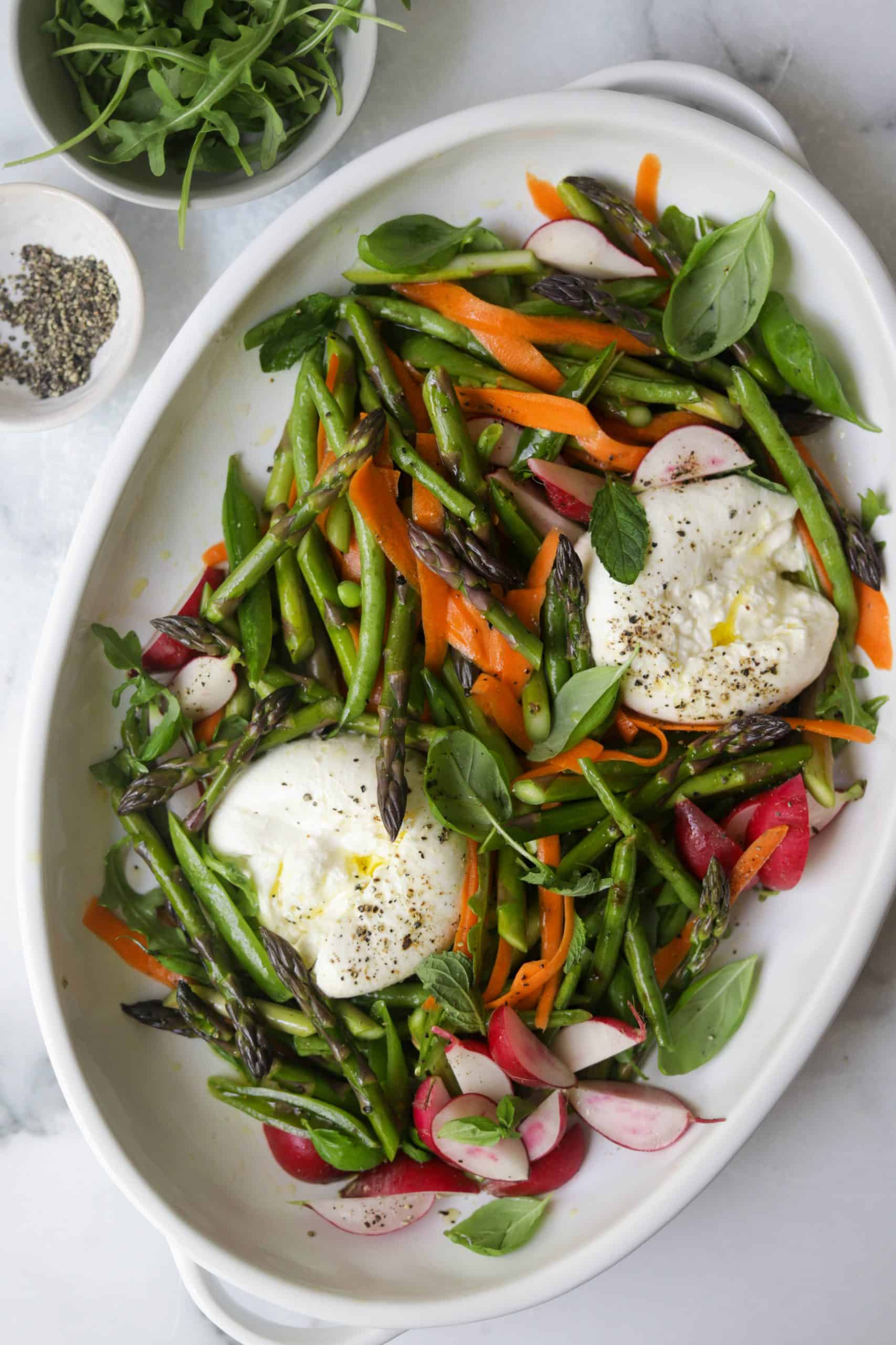 A white platter filled with spring vegetables, burrata cheese and herbs.