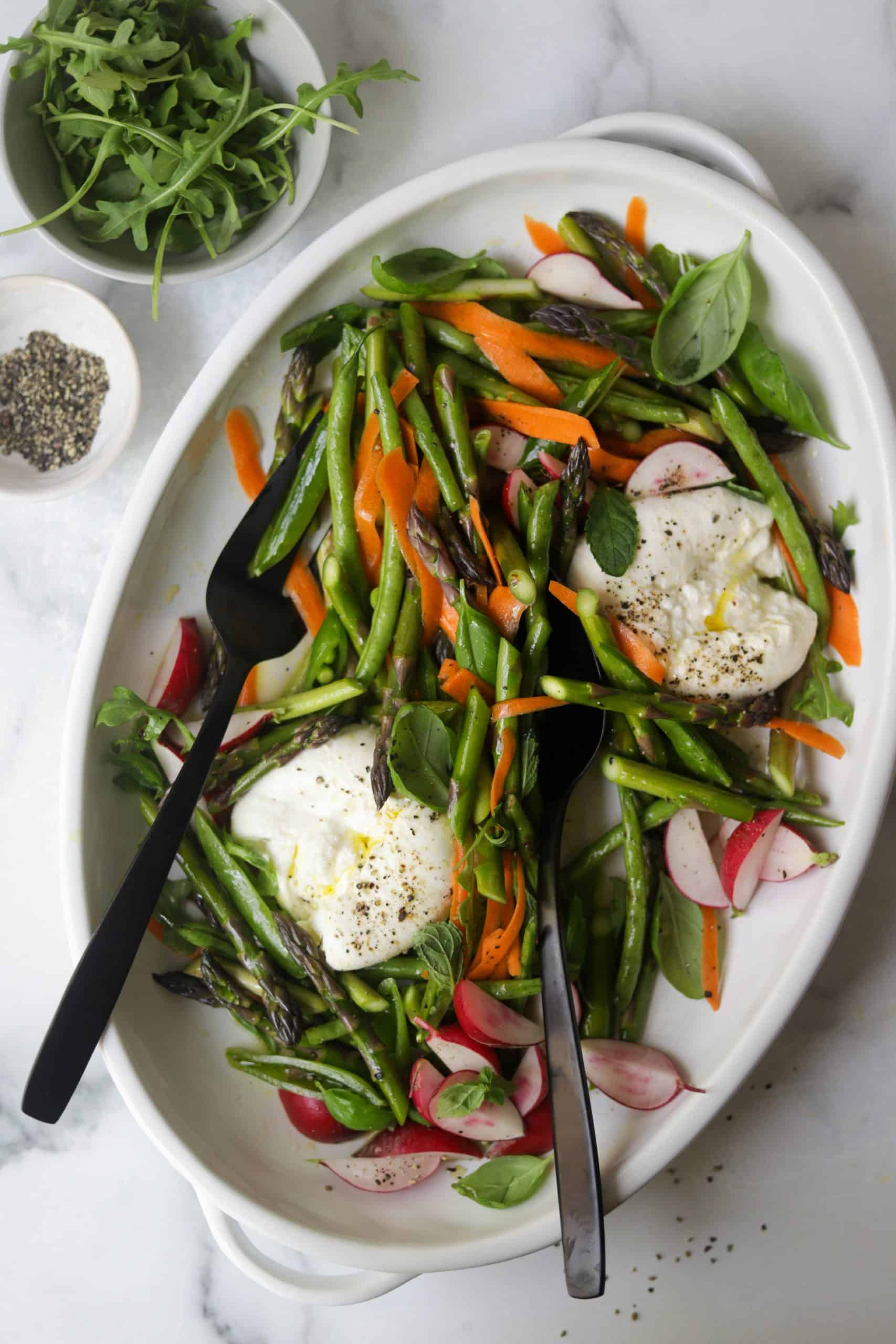 A white platter filled with spring vegetables, burrata and herbs.