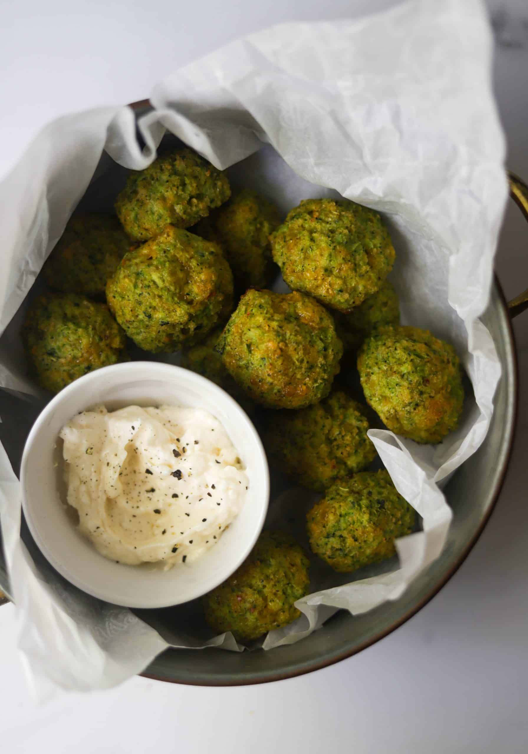 A container full of broccoli bites with a bowl of aioli.