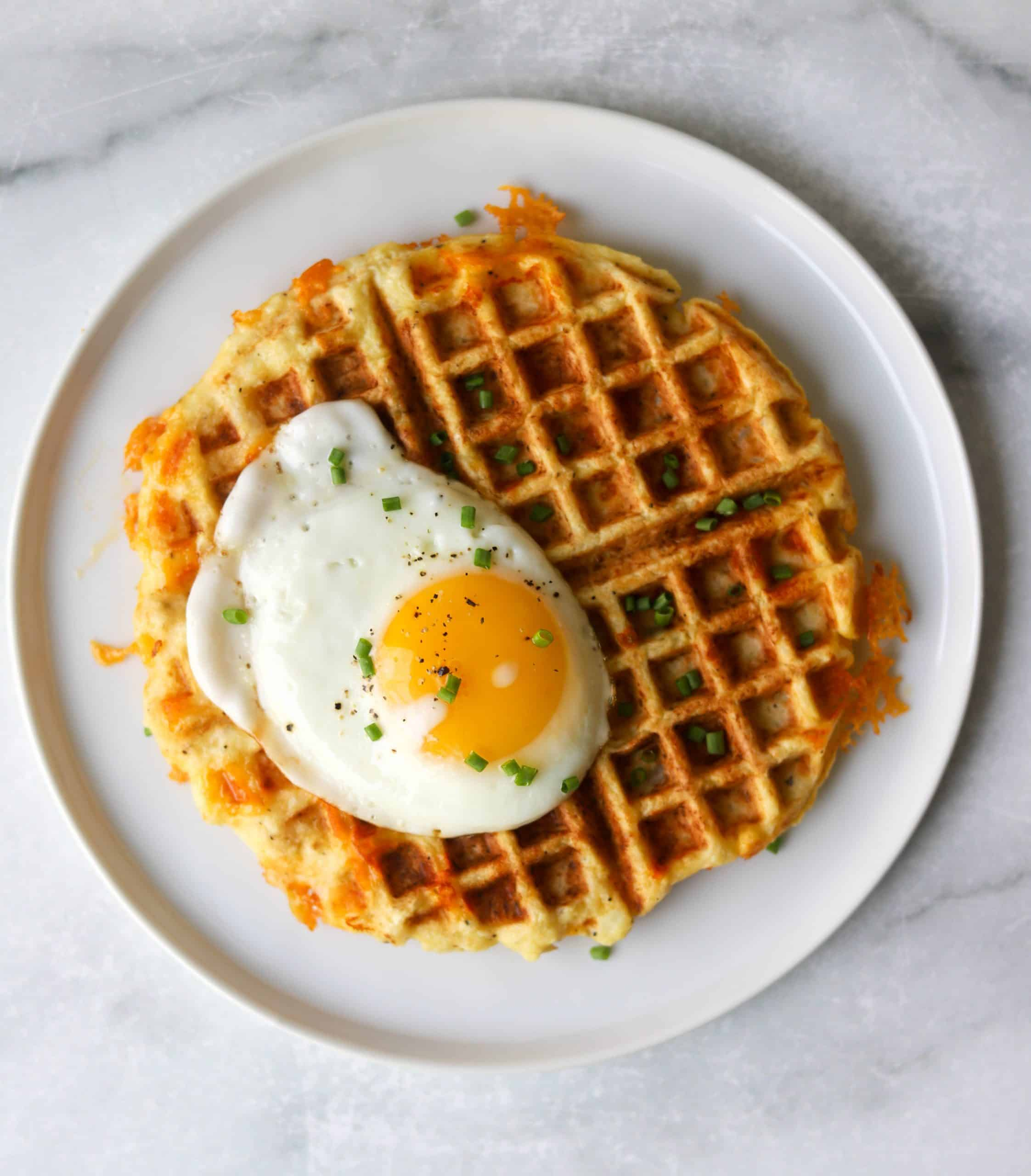 A cauliflower waffle with crisp cheesy edges on a white plate with a fried egg and chives on top.