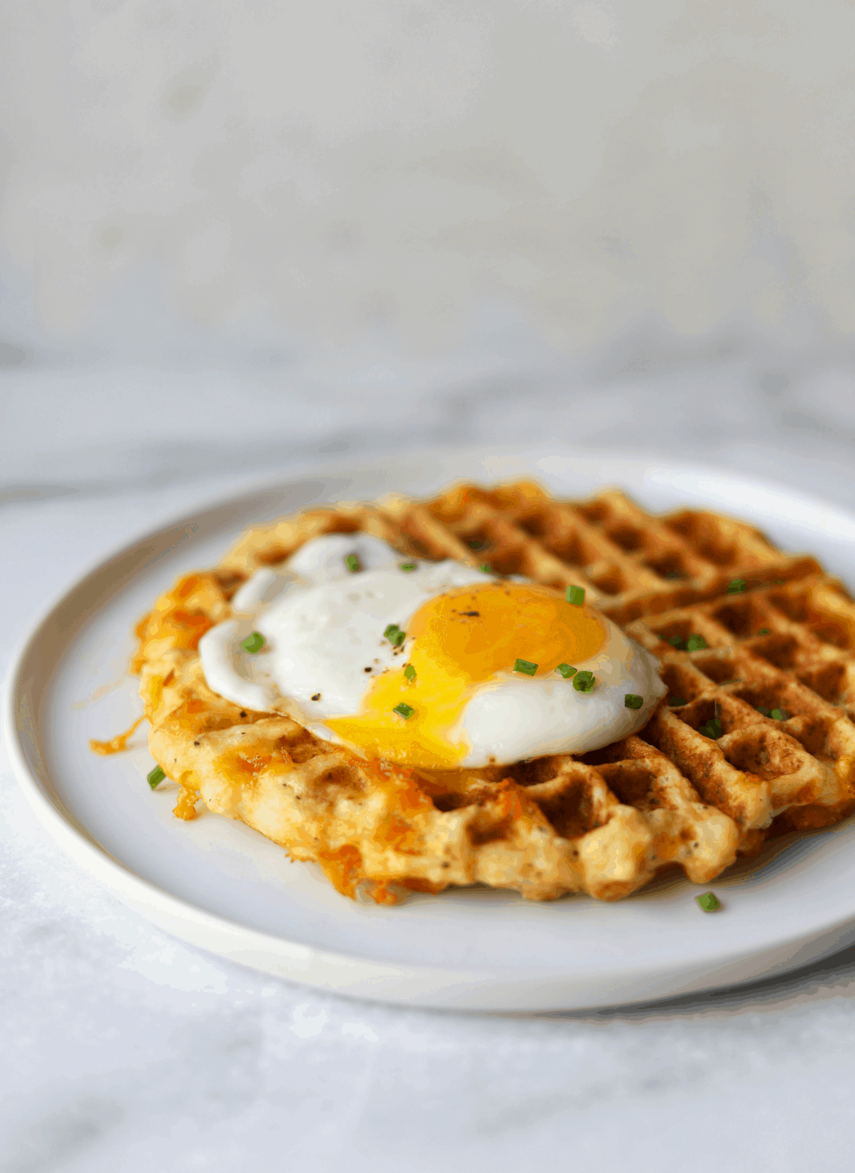 A side shot of a cauliflower waffle with a fried egg and chives on top.