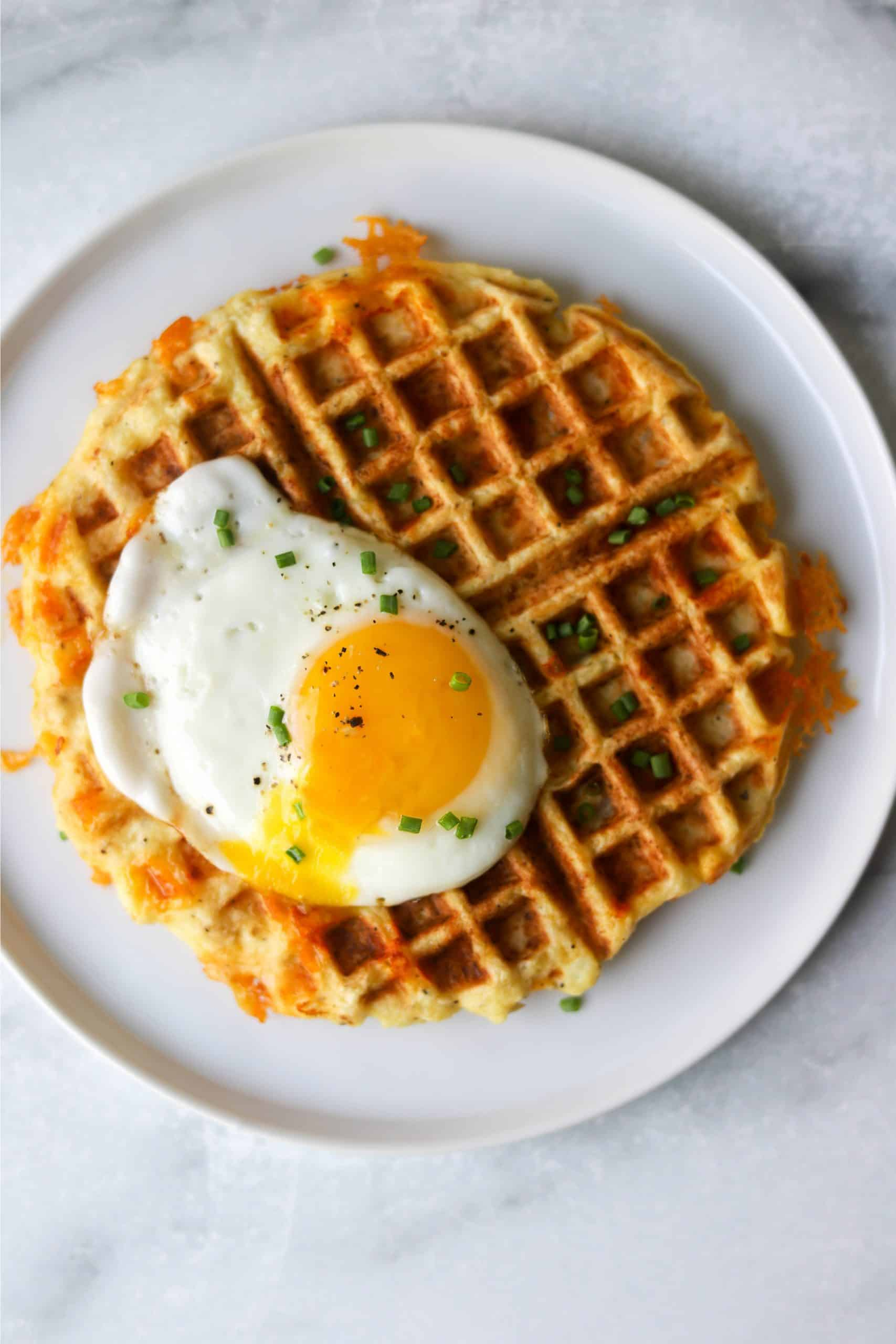 An overhead shot of a cauliflower waffle with a fried egg and chives on top.