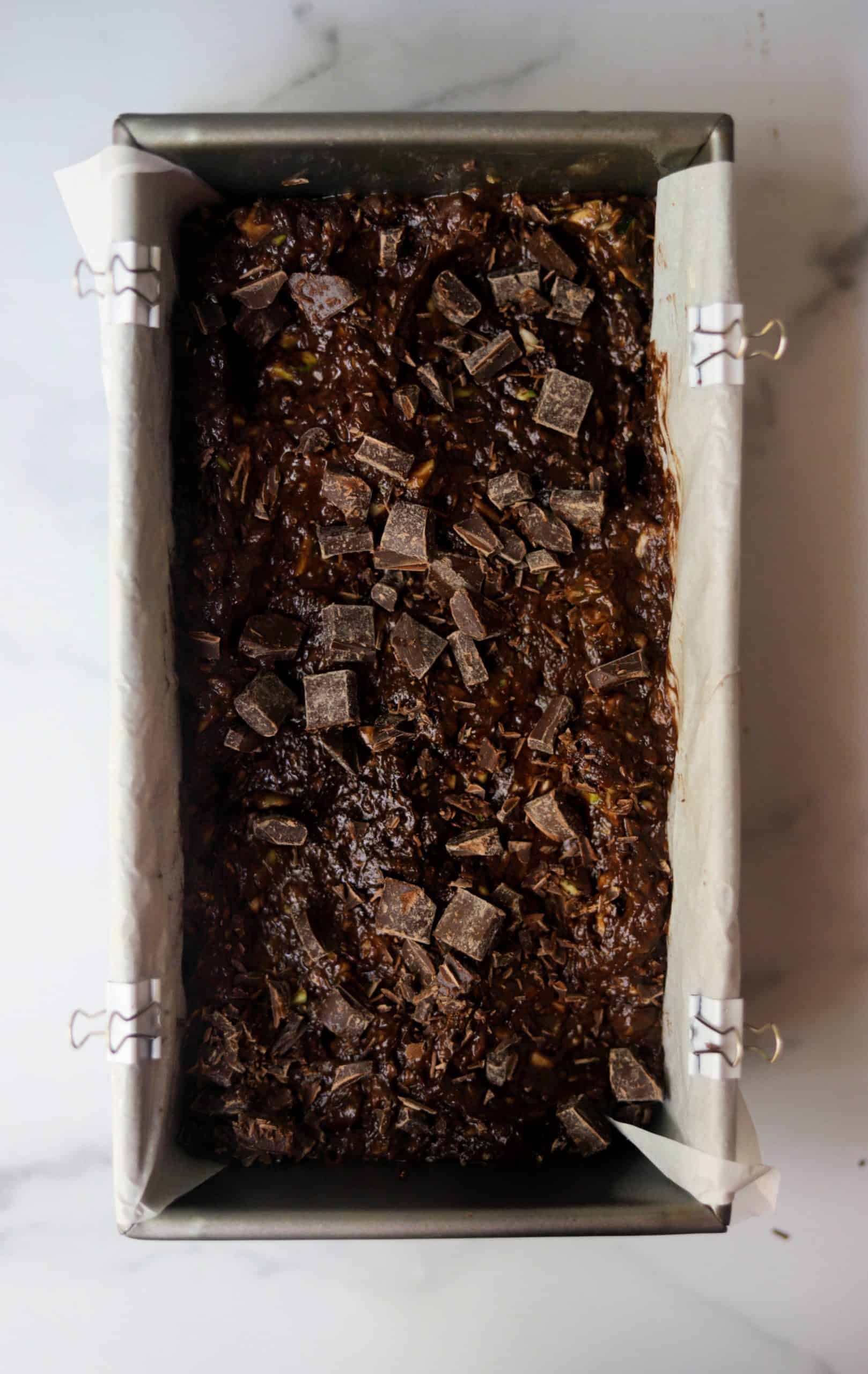A loaf tin filled with double chocolate zucchini bread batter.
