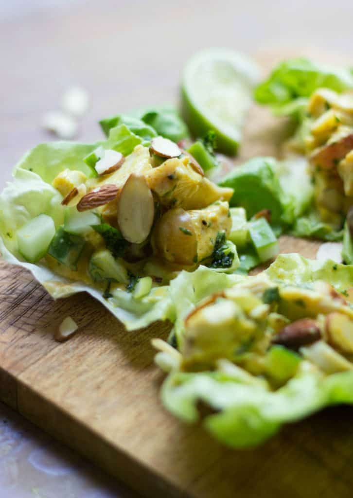 Close up of turkey salad lettuce wraps on a wood cutting board.