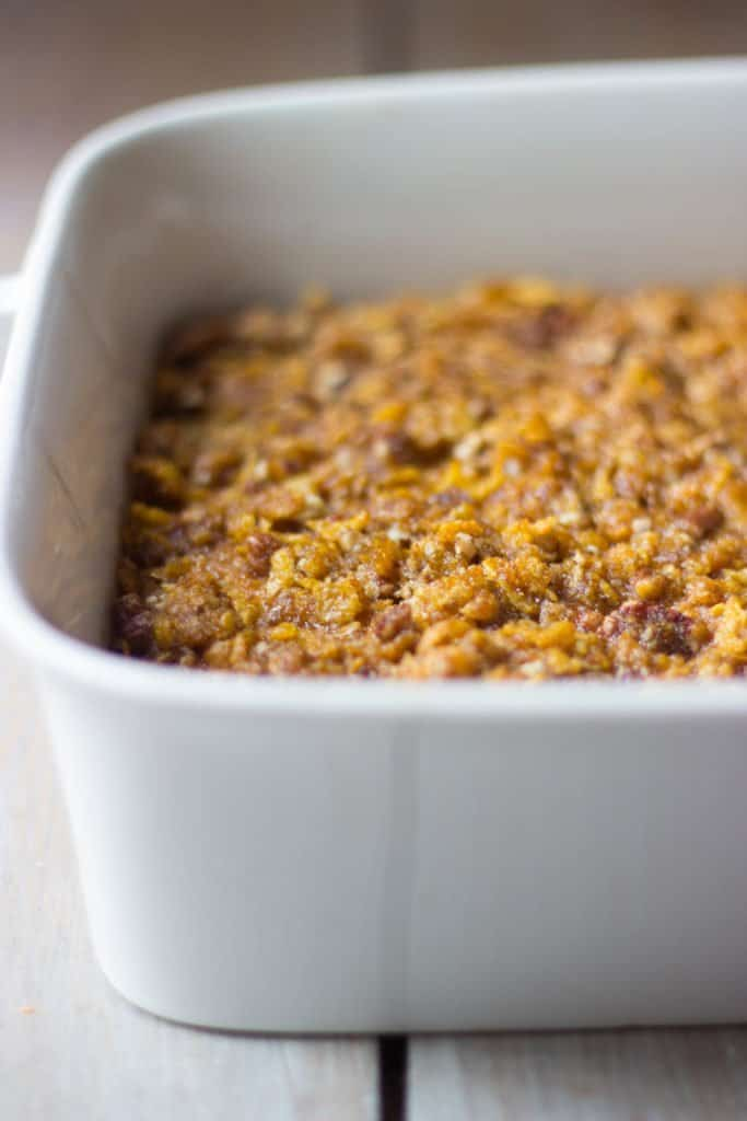 Angle close-up shot of sweet potato casserole in white baking dish with crispy topping.