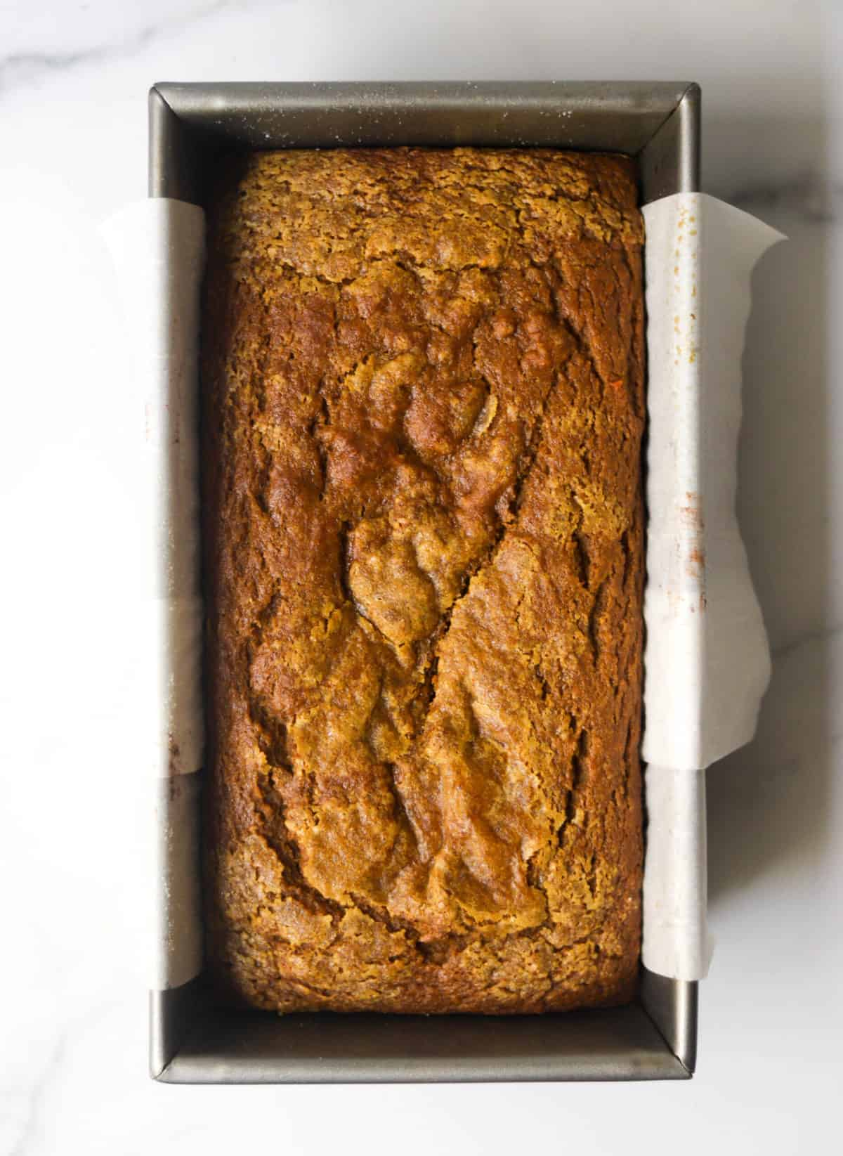 A loaf pan with spiced pumpkin bread.