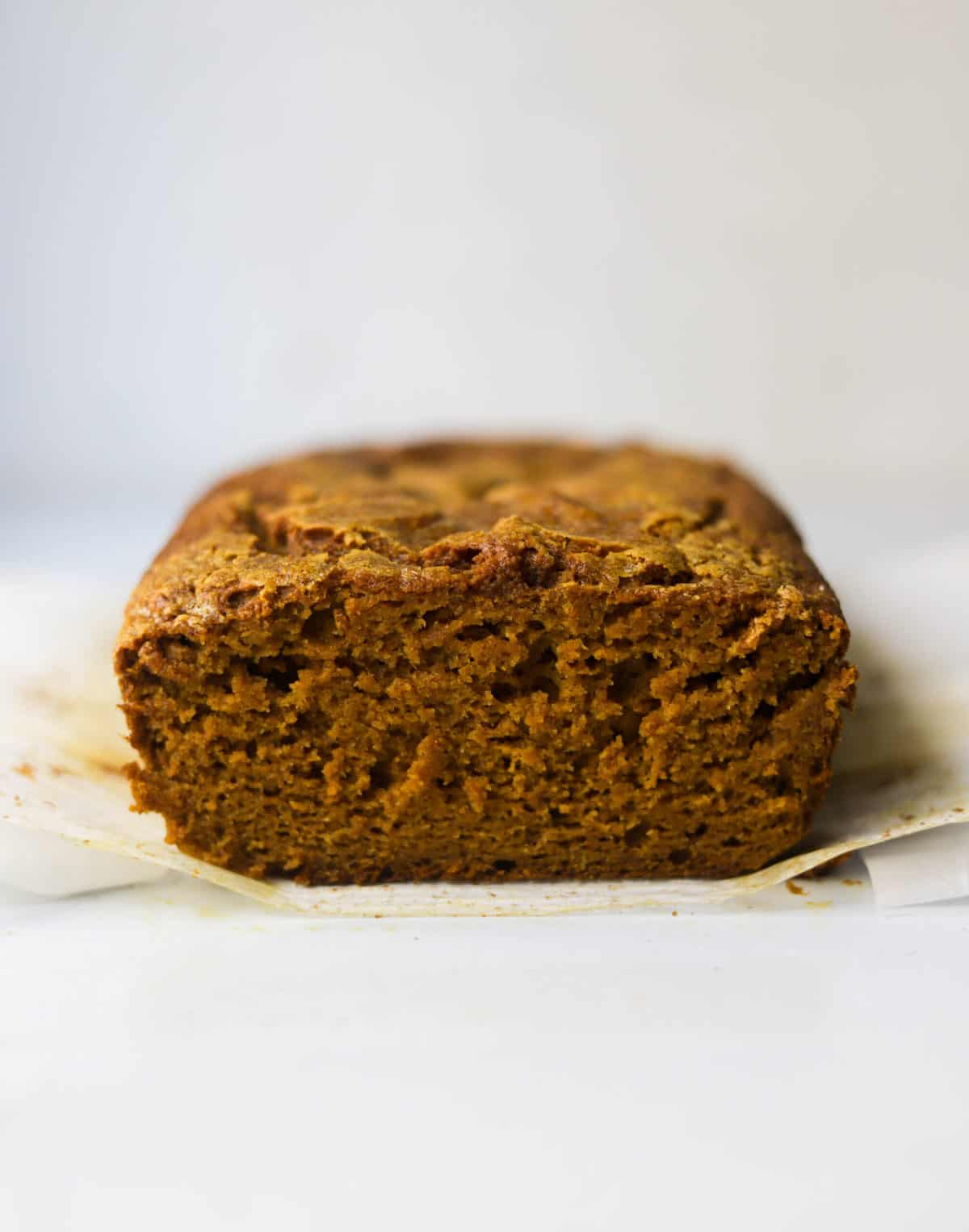 A side shot of a loaf of pumpkin bread with one slice.