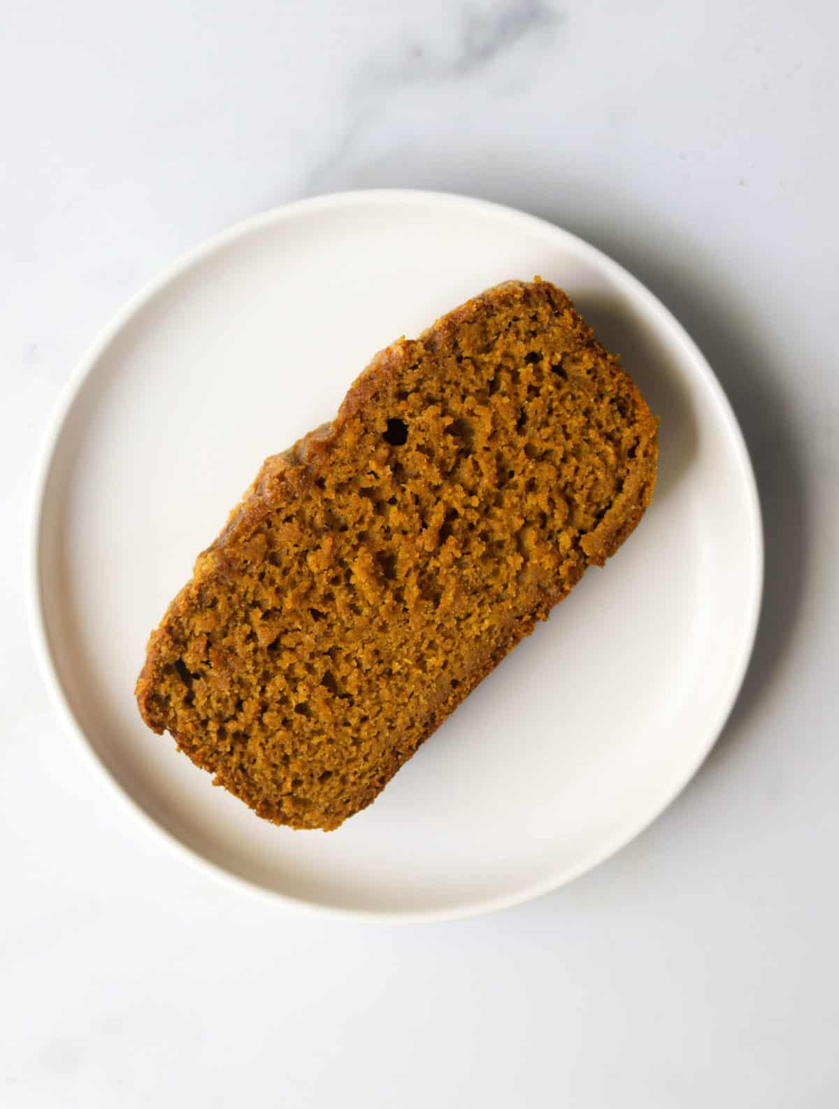 One slice of pumpkin bread on a white plate.
