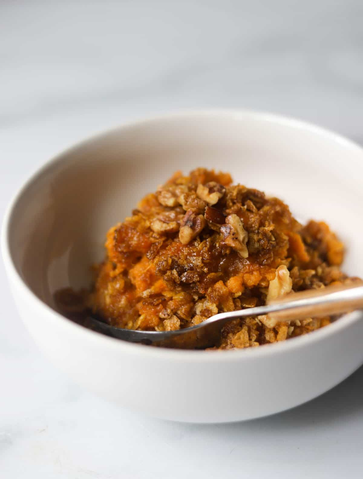 A side shot of a scoop of sweet potato casserole in a white bowl.