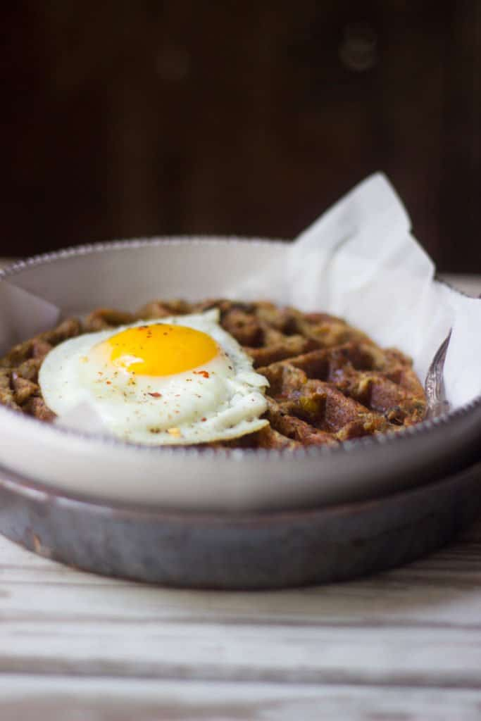 Angle shot of an egg on top of leftover stuffing waffle on a plate.