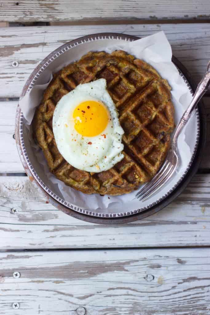 Overhead shot of leftover stuffing waffle with an egg on top on a plate.