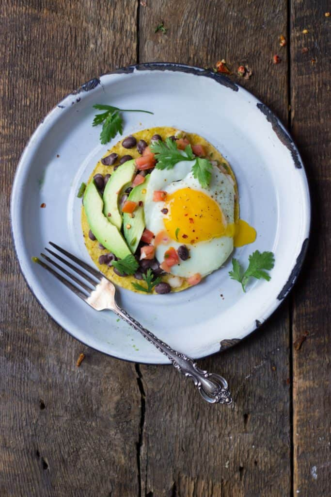 Overhead shot of loaded breakfast tostadad with a runny egg.