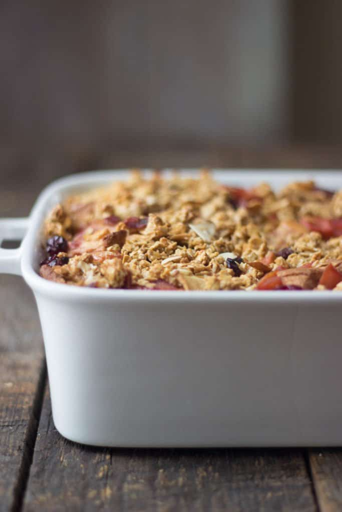 Side shot of Apple Cranberry Bread Pudding in a white baking dish.