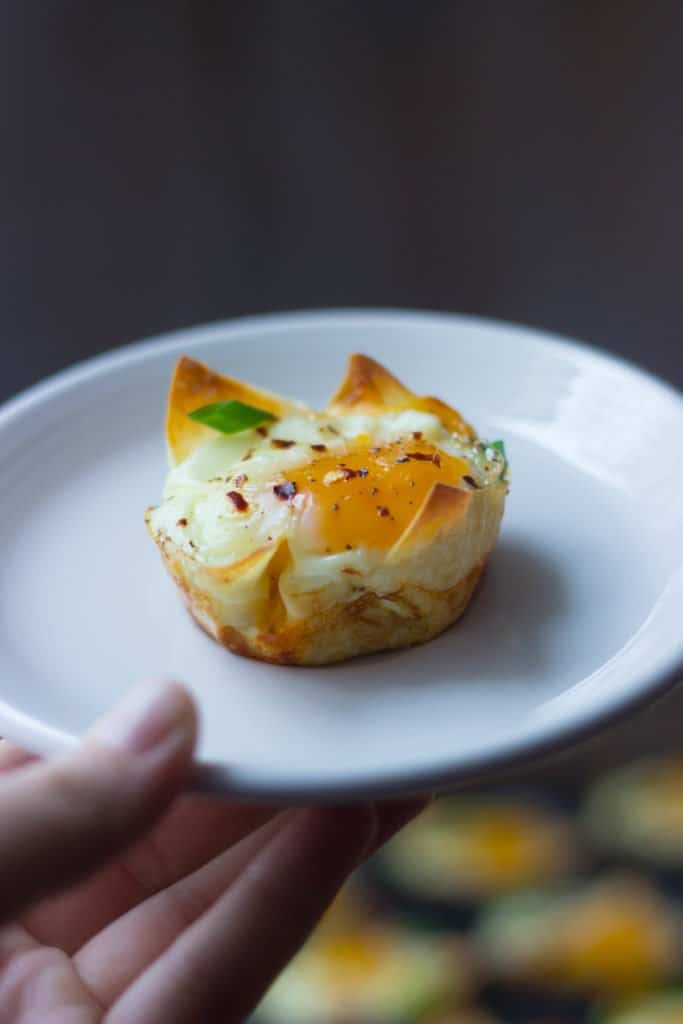 Angle shot of one cheesy wonton breakfast cup on a white plate.