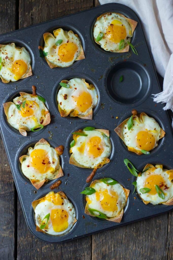 Overhead shot of cheesy breakfast wonton cups in a muffin tin pan.