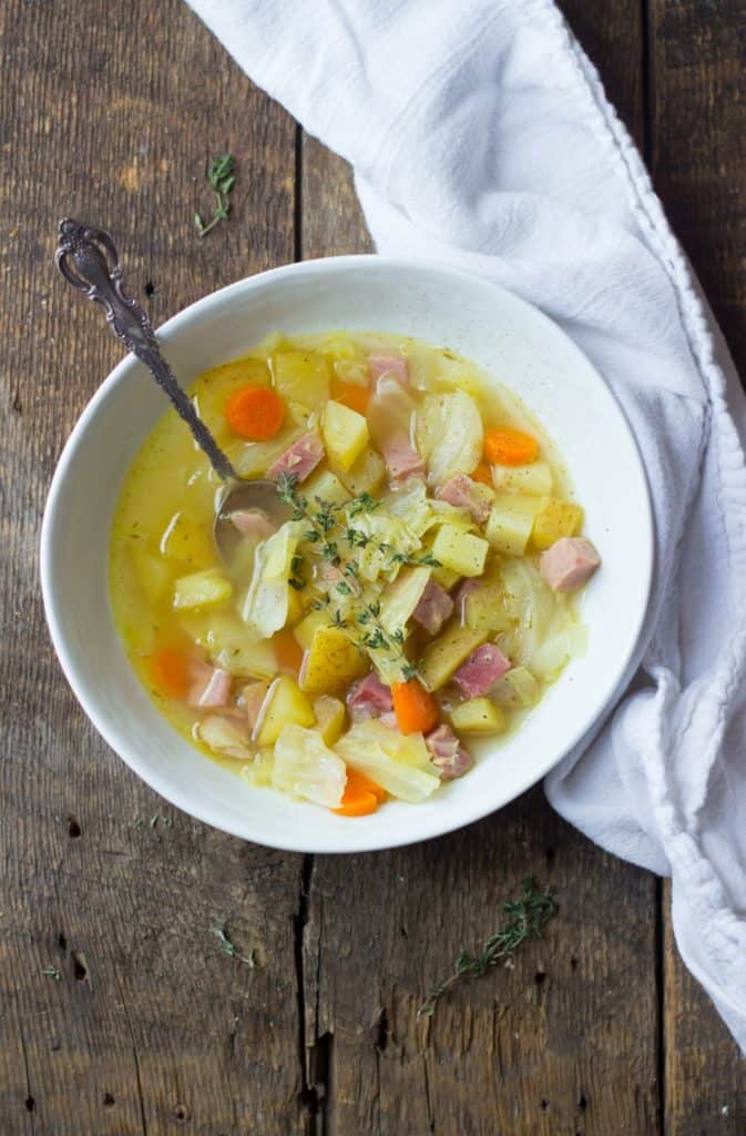 Serving of ham, cabbage, and potato soup in a white bowl.