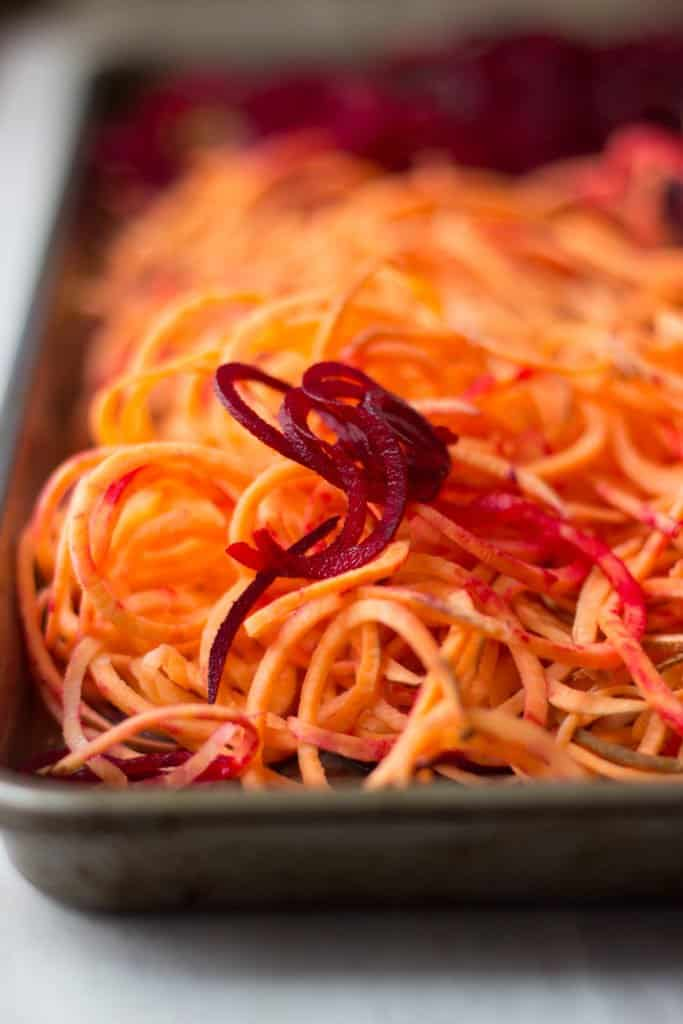 Sweet potato and beet curly fries on a baking sheet