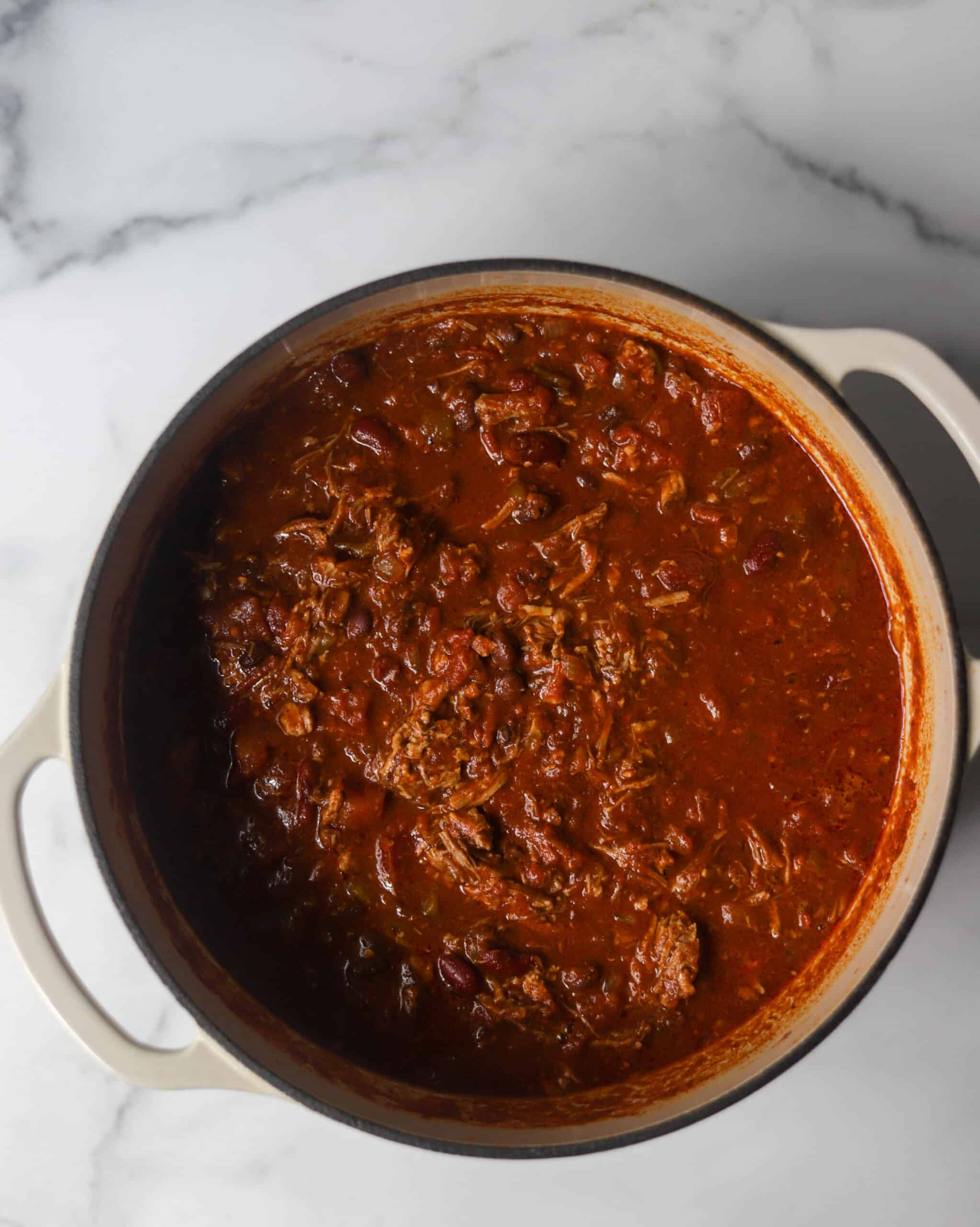 A white pot filled with pulled pork chili.