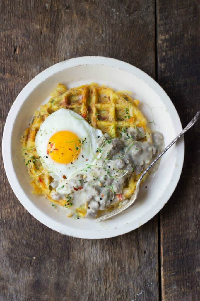 Hash brown waffle, turkey sausage gravy and a fried egg on a white plate