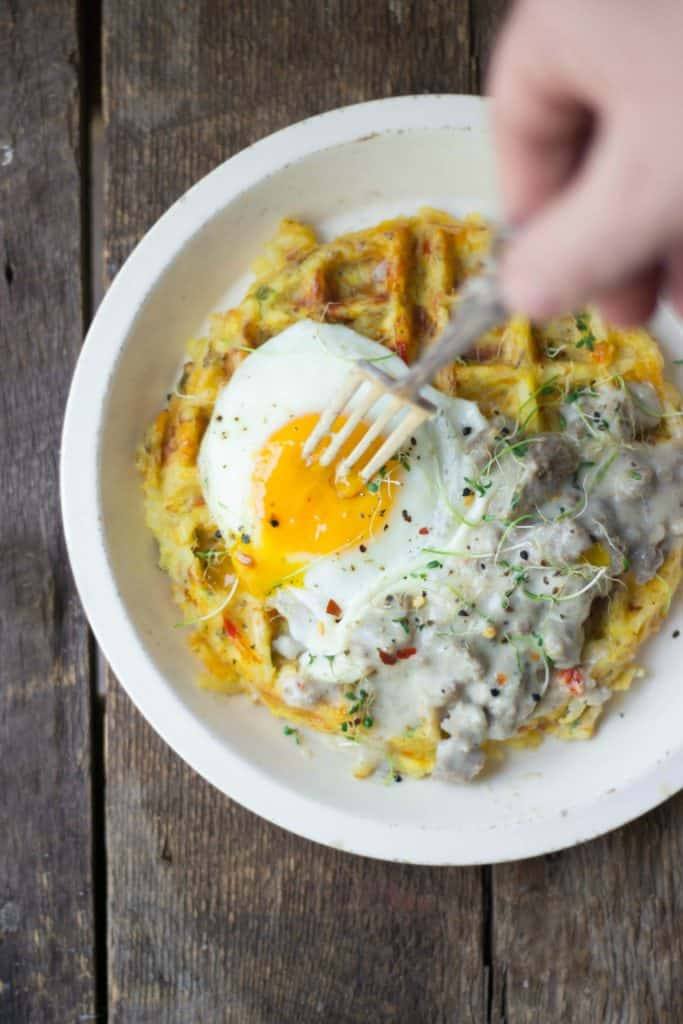 Hash brown waffle, turkey sausage gravy and fried egg on a white plate